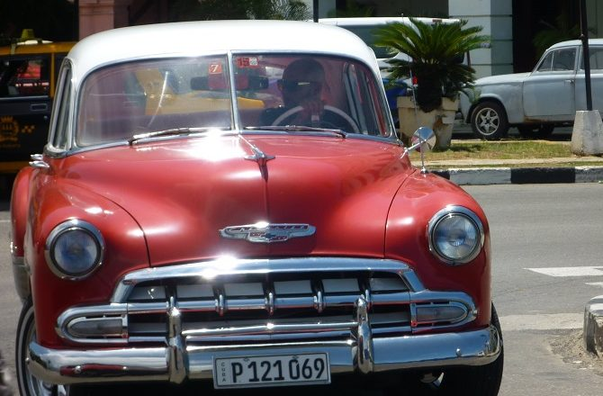 A bright red classic American car in Old Havana