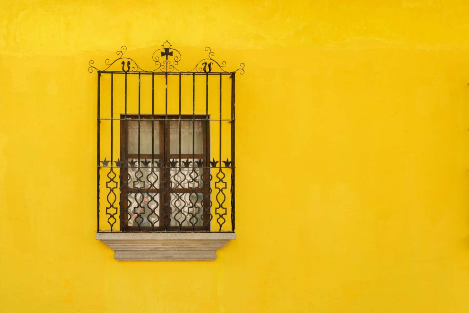 Window on yellow wall in Antigua, Guatemala