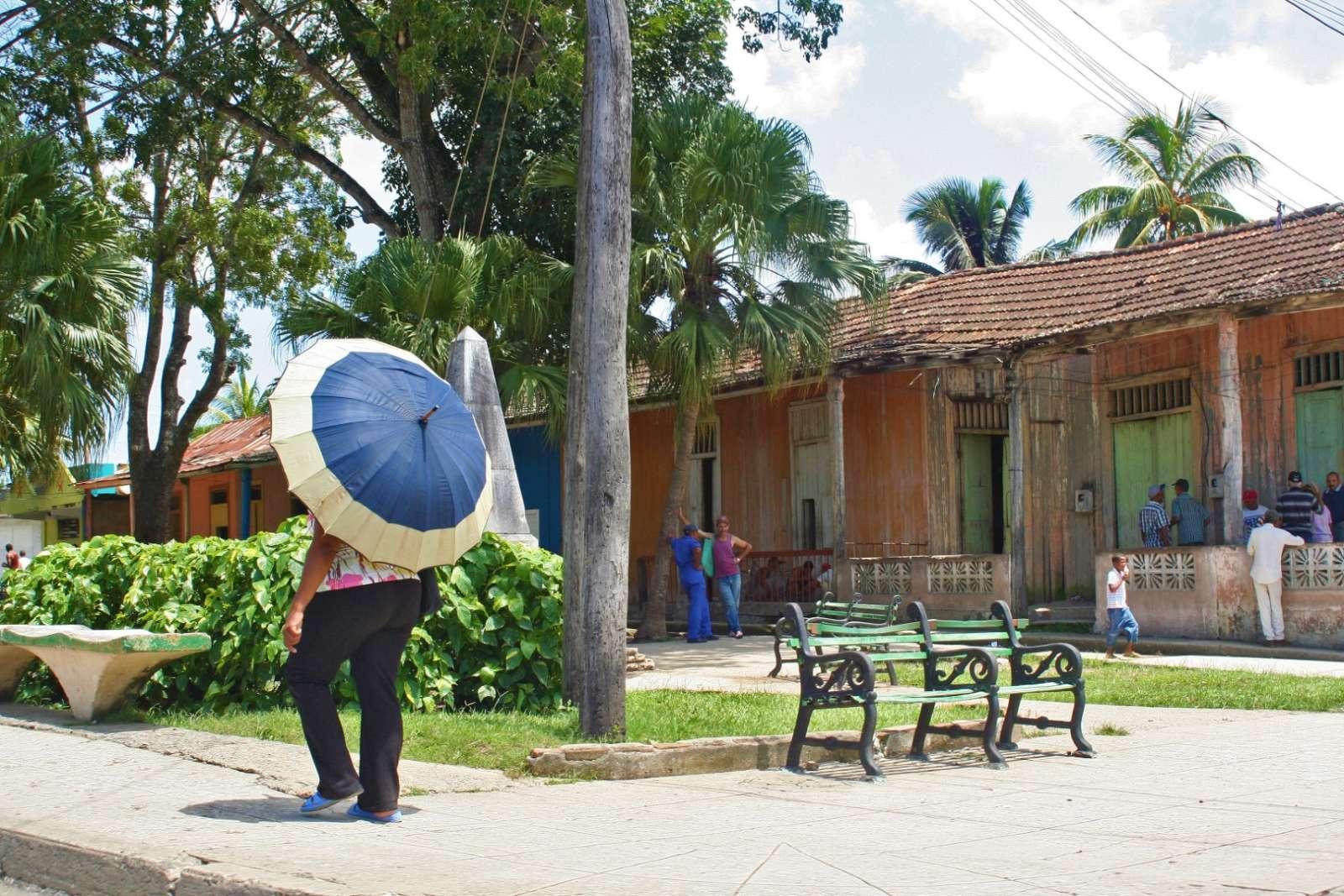 Woman with umbrella walking in Baracoa