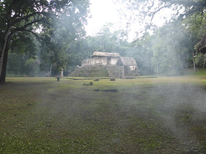 The Mayan ruins at Ceibal with the smoke of natural mosquito repellent