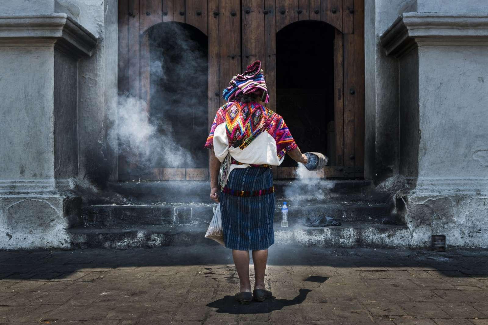 Mayan woman praying in front of Santo Tomas church at Chichicastenango, Guatemala