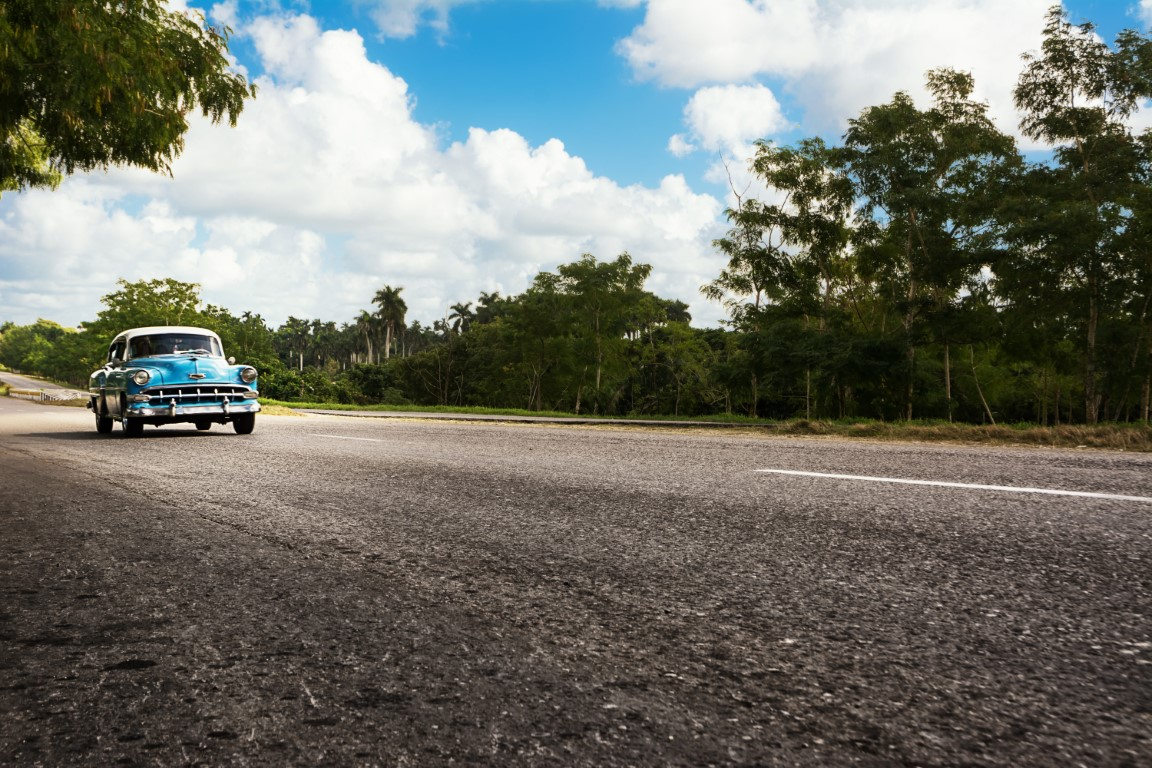 Classic car driving along an empty road in Cuba