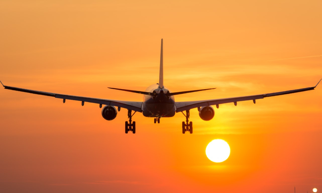 Airplane departing into the sunset