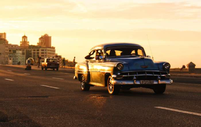 A classic car driving along Havana's seafront Malecon
