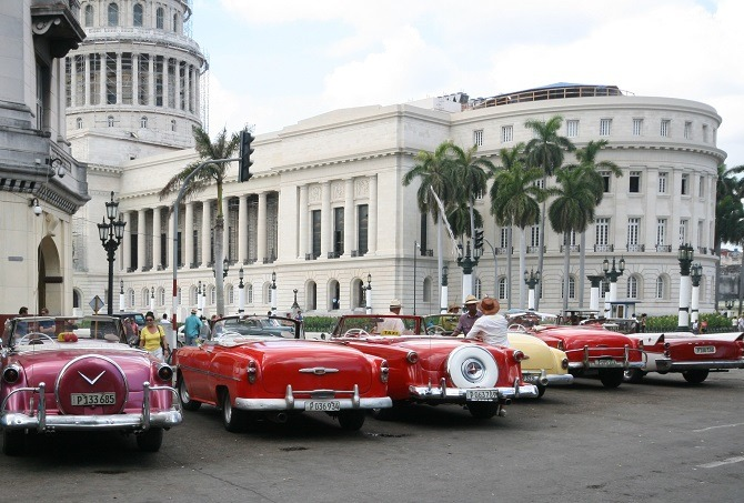 A row of classic American cars in front of the Capitol building in Havana