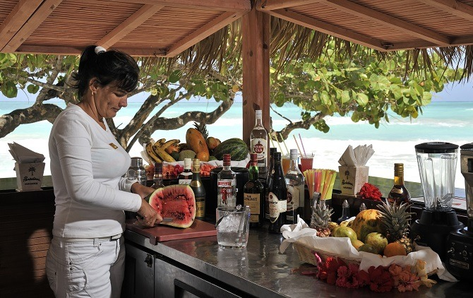 woman at cuba beach bar slicing a melon