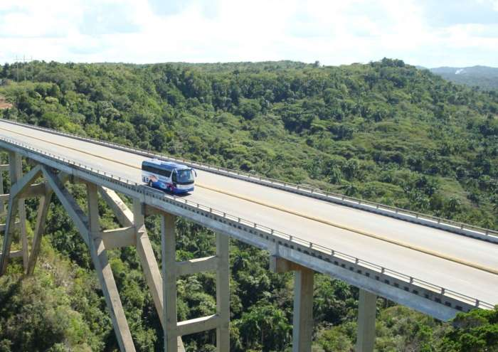 A coach driving over a bridge in Cuba