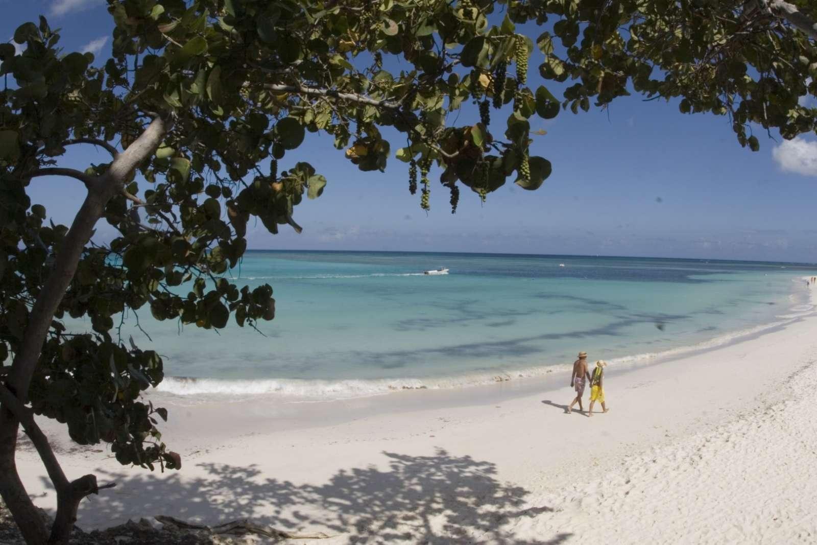 Couple walking along a beautiful beach in Guardalavaca, Cuba