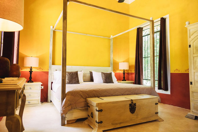 Bedroom with yellow walls at Hacienda Ticum near Izamal