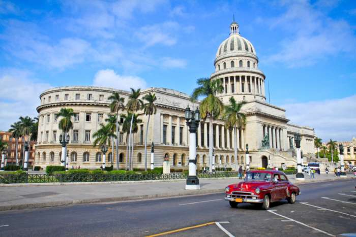Old taxi driving past the Capitol building in Old Havana
