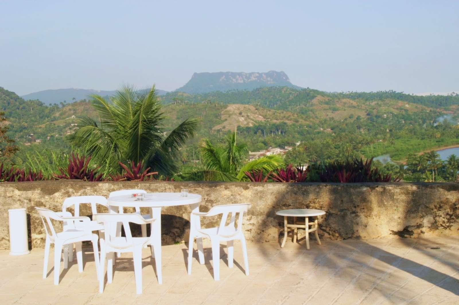 Table and chairs facing El Yunque at Hotel El Castillo