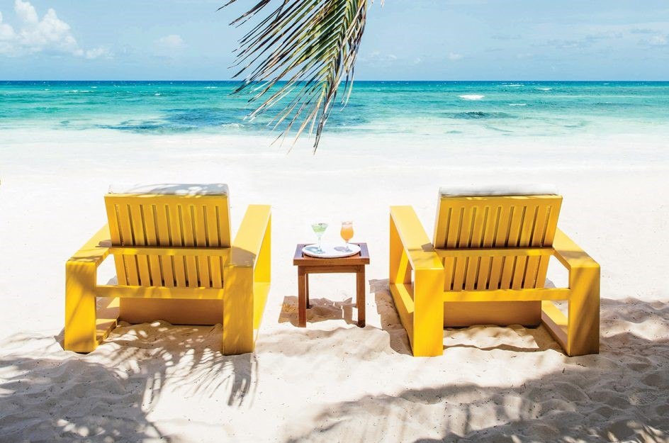 Two chairs facing the sea on the beach at Hotel Esencia
