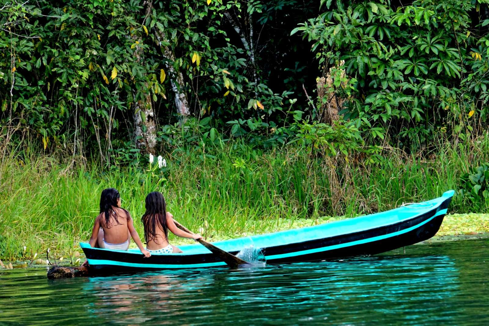 Two young girls in canoe on Rio Dulce, Guatemala