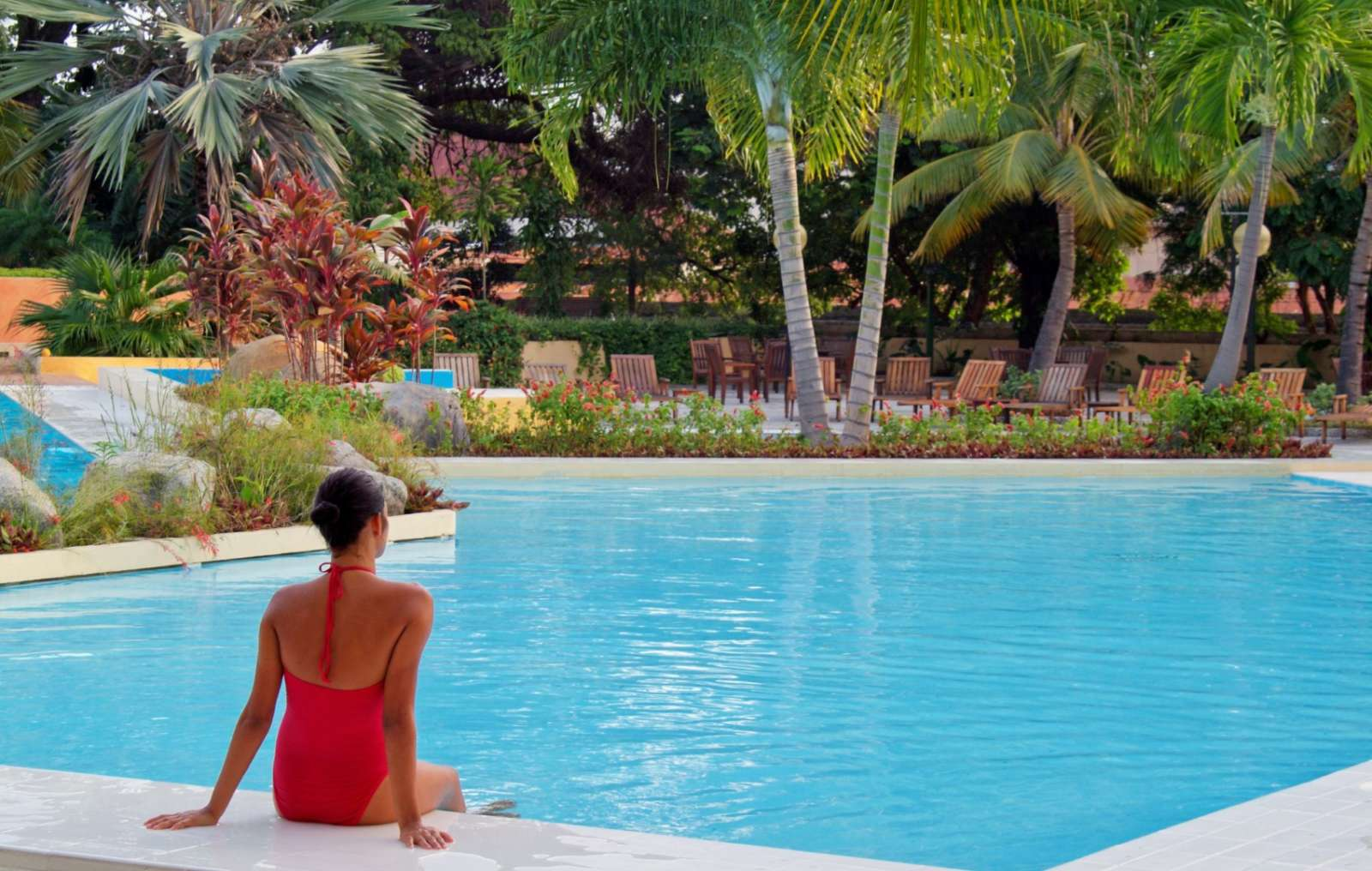 Woman sat facing pool at Melia Santiago