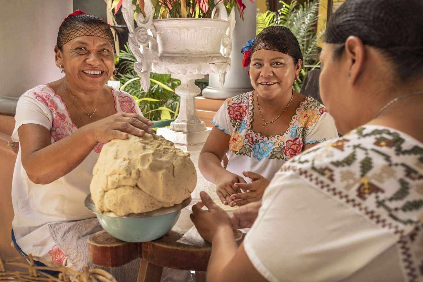 Three Mayan women making tortillas