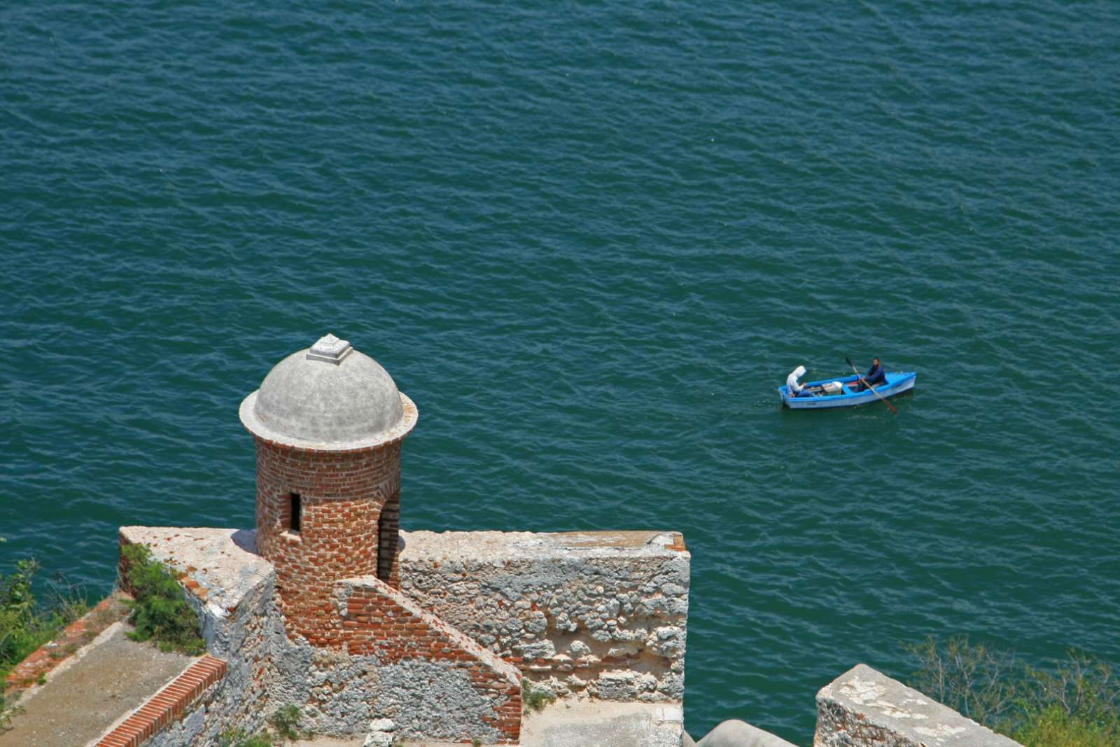 Small boat passing under San Pedro fort in Santiago de Cuba