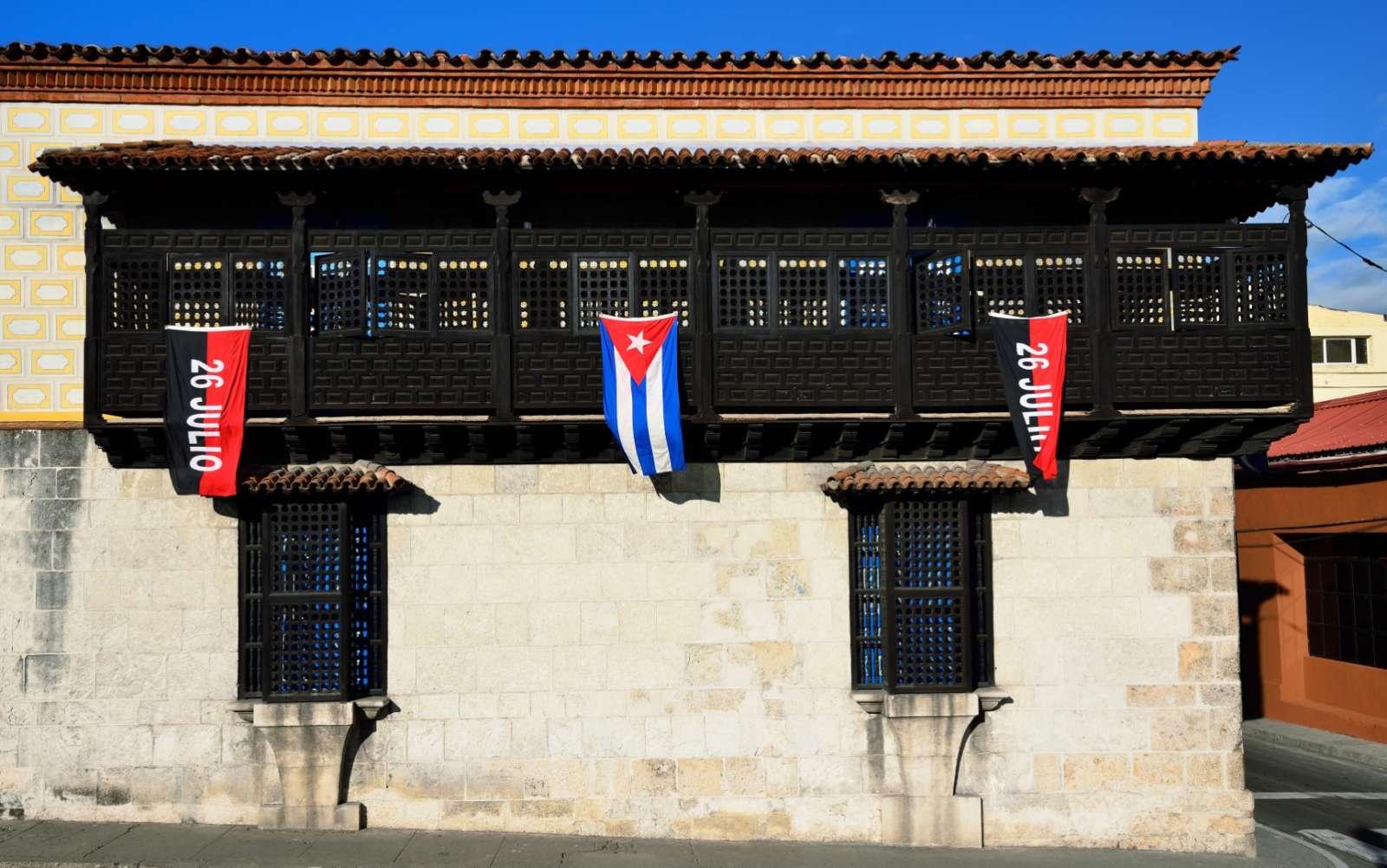 Flags on colonial building in Santiago de Cuba
