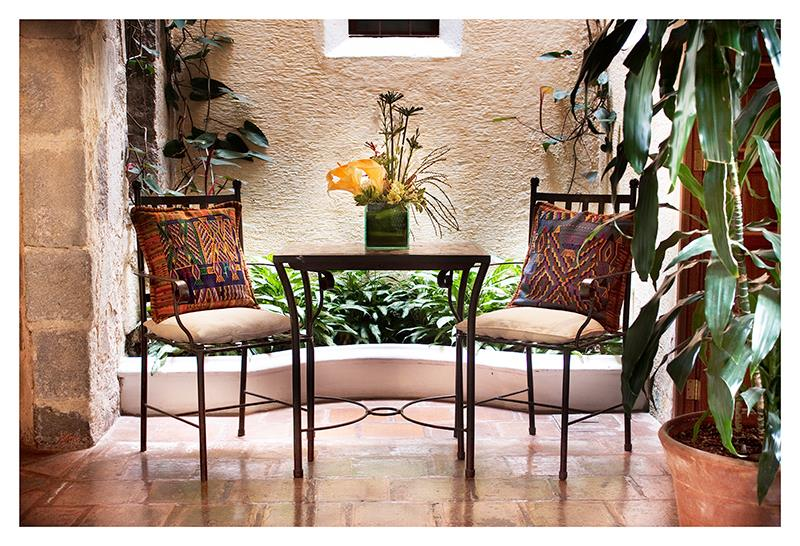 Two iron chairs with colourful cushions at Hotel Meson de Maria in Antigua