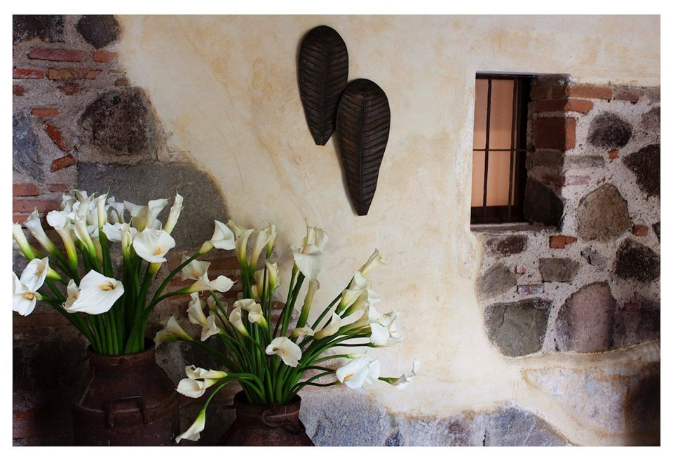Flowers and wall carvings at Hotel Meson de Maria in Antigua
