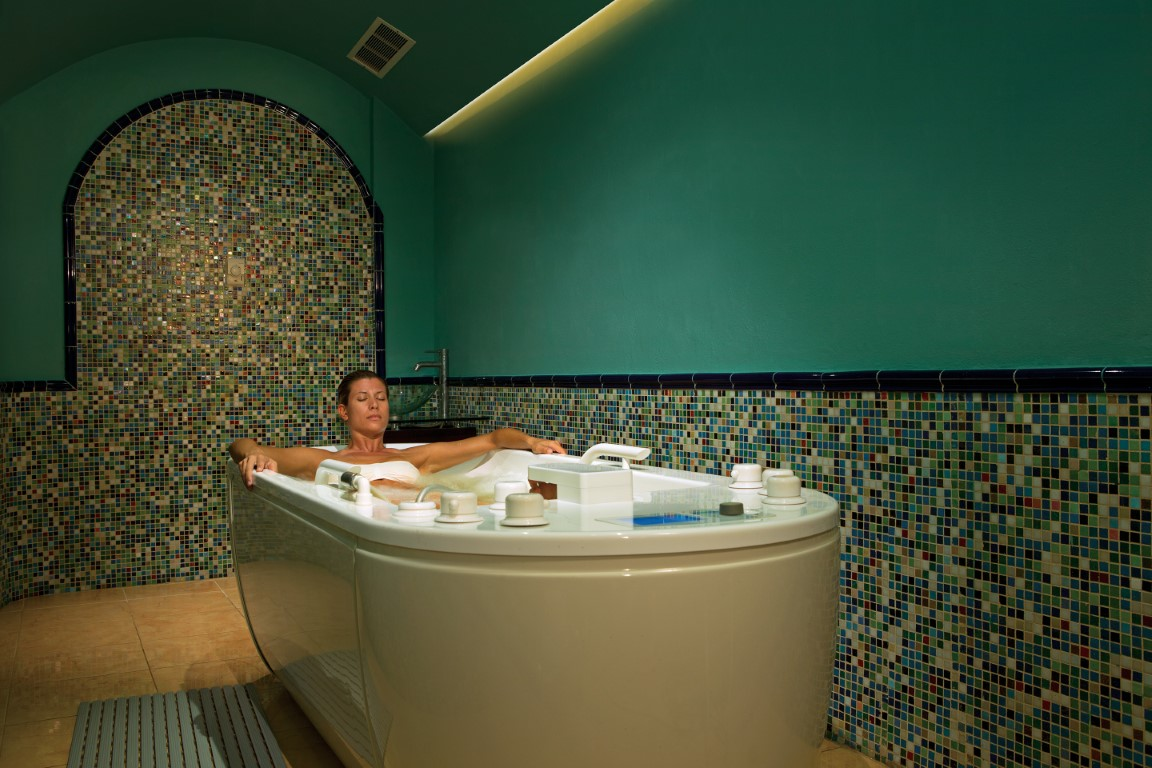 Woman soaking in a spa tub at Zoetry Villa Rolandi