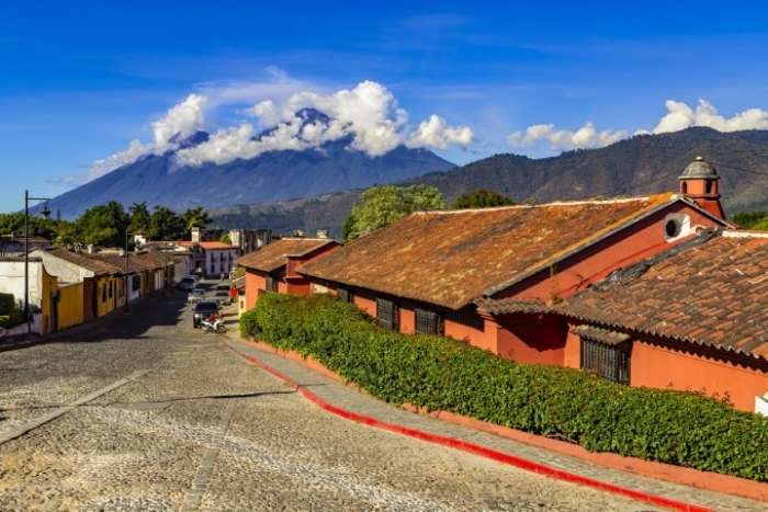 A quiet cobbled street in the Guatemalan town of Antigua with two volcanoes in the background