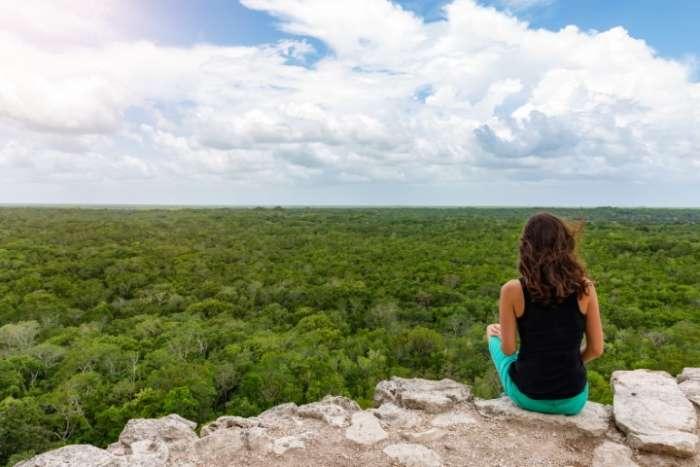 Woman on top of pyramid at Coba Mayan ruins