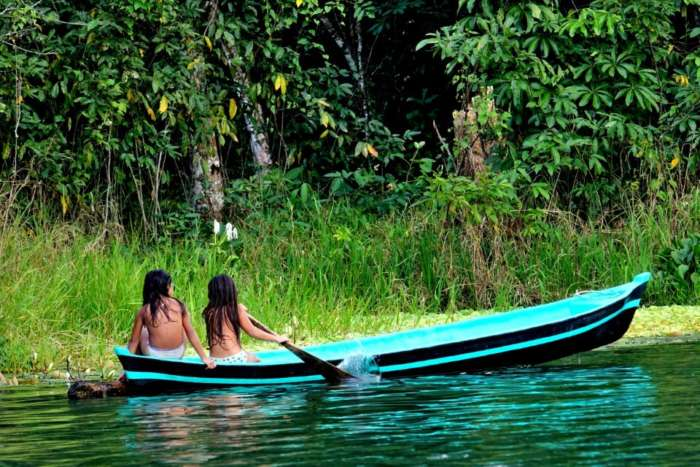 Two girls in a canoe on the Rio Dulce near Livingston