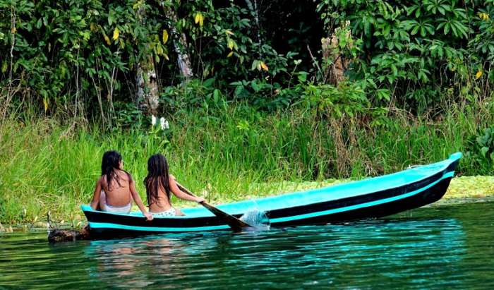 Two girls in a canoe on the Rio Dulce in Guatemala
