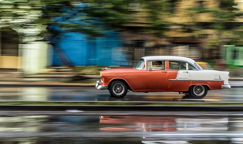 Classic, old car driving along a wet road in Cuba