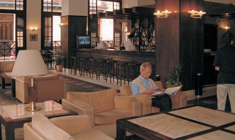Man reading newspaper in hotel lobby