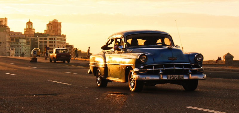Car driving along the Malecon at sunset
